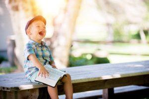 dziecko śmiejące się siedzące na ławce